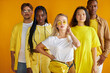 confident diverse mult-ethnic group of people stand together, isolated on yellow background, stylish african caucasian and asian youth