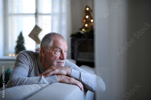 Fotografie, Obraz Lonely senior man sitting on sofa indoors at Christmas, solitude concept