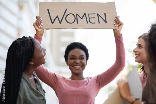 Fototapeta Cheerful black woman holding placard, fighting for women rights