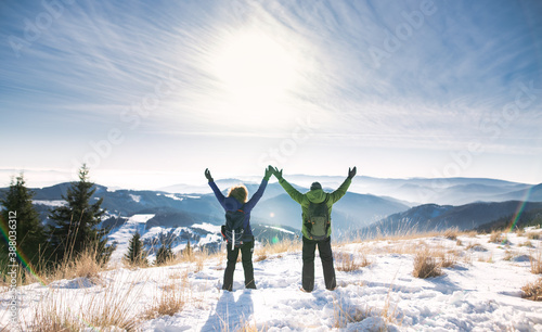 Fotografering Rear view of senior couple hikers in snow-covered winter nature, stretching arms