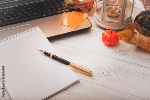 Foto laptop, Notepad, pen, pumpkins, candle on a white  table, fall still life