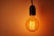 Leinwandbild Motiv Vintage light bulb on orange background, copy space. Glowing edison bulb