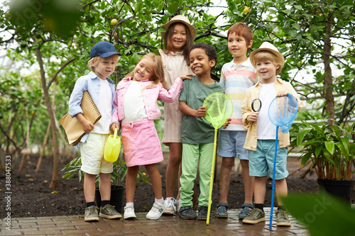 happy multi-ethnic group of children have fun, walk in garden or greenhouse, get Canvas Print