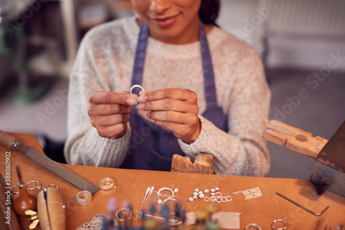 Obraz Close Up Of Female Jeweller At Bench Checking Ring She Is Working On In Studio - fototapety do salonu