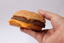 Hand Holding A Royal Hamburger With Cheese And Grilled Cutlet