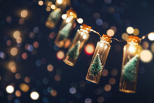Christmas And New Year Concept, Close-up, Elegant Christmas Tree In Glass Jar With Bokeh Lights Background, Copy Space.