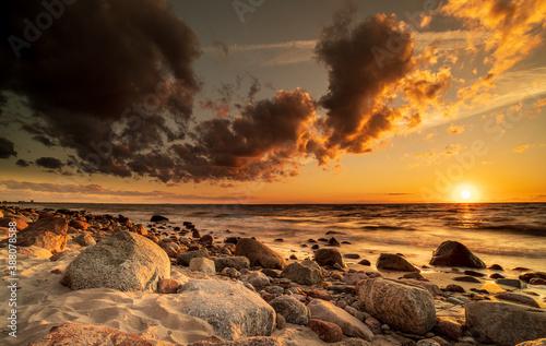 Obraz Zachód słońca nad morzem. Kamienie, piasek i morze rozświetlone promieniami zachodzącego słońca.  - fototapety do salonu