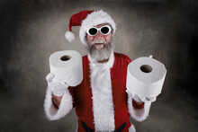 Santa Claus Wearing Sunglasses And Holding Rolls Of Toilet Paper As Gifts During Pandemic