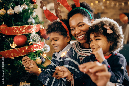 Photo Happy African American family using sparklers while celebrating Christmas at home