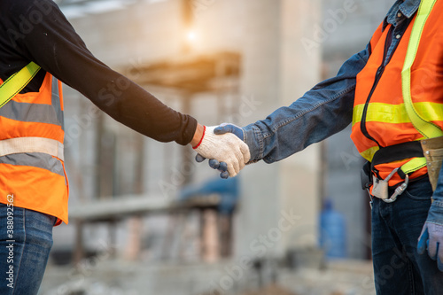 Foto Close up two engineers builders hands in gloves greeting each other with handshake at construction site