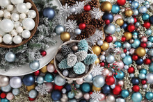 Top View Christmas Decorations Centerpiece With Garland And Balls Near A Basket With Pine Cones, Isolated On A Heap Of Colorful And Shiny Balld