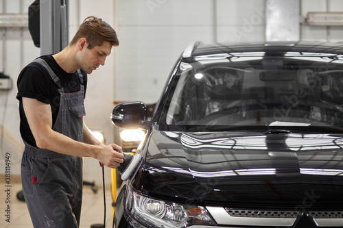 hard-working auto mechanic worker polishing car at automobile repair service, renew service station shop by power buffer machine, alone