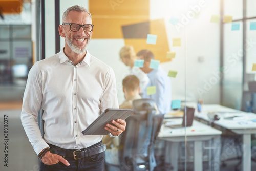 Obraz Happy mature businessman in classic wear holding digital tablet, looking at camera and smiling while standing in the modern office - fototapety do salonu