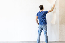 A Man Tears Off Old Wallpaper From The Wall During Renovation, Image With Copy Space