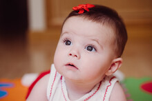Close-up Of Cute Baby Girl With Red Hair Clip Looking Away While Lying At Home