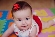 Close-up Of Cute Smiling Baby Girl Lying On Puzzle Playmat At Home
