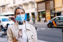 Female Journalist Wearing Mask With Microphone Looking Away While Standing On Street In City