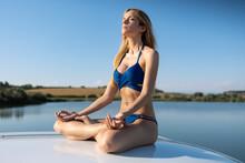 Young Woman In Bikini Meditating While Sitting On Car Roof