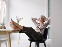 Businesswoman With Hands Behind Head Relaxing On Chair In Loft Office