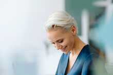 Close-up Of Smiling Businesswoman Looking Down In Office