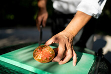 Close-up Of Male Chef Holding Tomato Slice On Cutting Board In Orchard