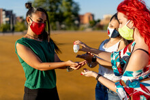 Friends Using Hand Sanitizer While Standing Outdoors On Sunny Day