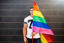 Young Man Holding Rainbow Flag...