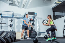 Male And Female Athletes Exercising With Medicine Ball In Gym