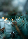 five lit white votive candles burning flames amid green pine branches and decorative pine cones