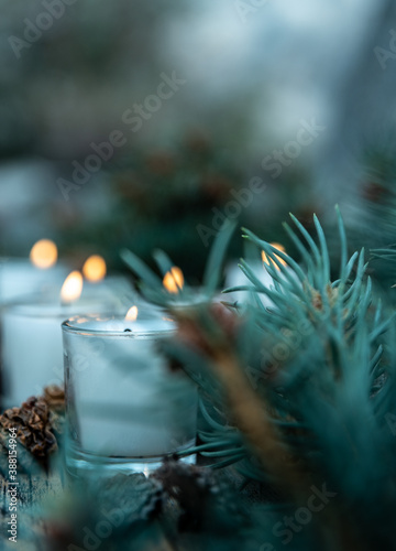 Fotografía five lit white votive candles burning flames amid green pine branches and decora