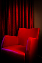 A Red Chair Infront Of Red Cur...