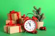 Leinwandbild Motiv Alarm clock with Christmas decor on green background. New Year countdown
