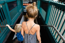Two Kids Walk Down The Steps At The Entrance To The New York City Subway