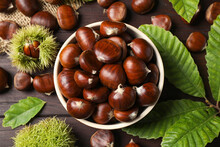 Fresh Sweet Edible Chestnuts On Brown Wooden Table, Flat Lay