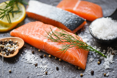 Fotografia Raw salmon filet with herbs and spices on dark black background