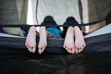 Close Up On Feets Of Two Children While Lying Down And Playing Together In Tent On Campsite. Holiday And Travel Family Camping Concept.