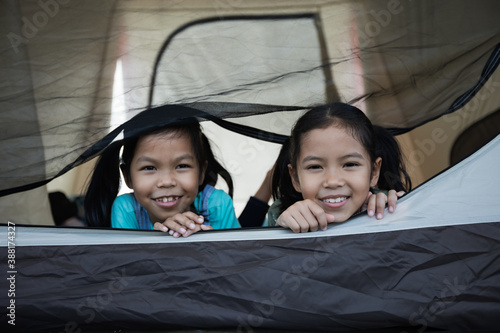 Tela Two cute asian child girl lying down and playing together in tent on campsite while camping with family