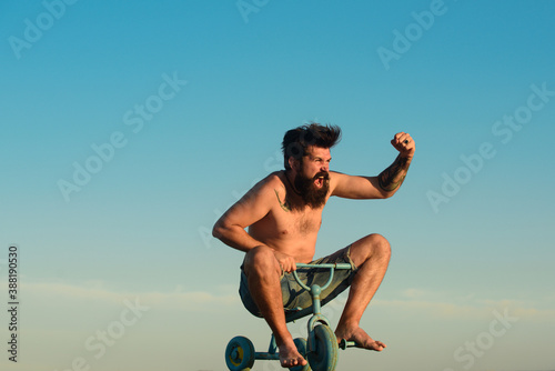 Papel de parede Excited young male riding a small bicycle and gesturing happiness