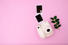 White Instant Camera With Green Leaf And Two Blank Photos For Design On A Pink Background. Cute Hipster Film Camera Flat Lay.