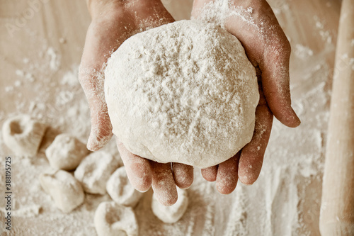 Fotografie, Obraz a woman chef is holding the dough, female hands are in flour, a female chef is h
