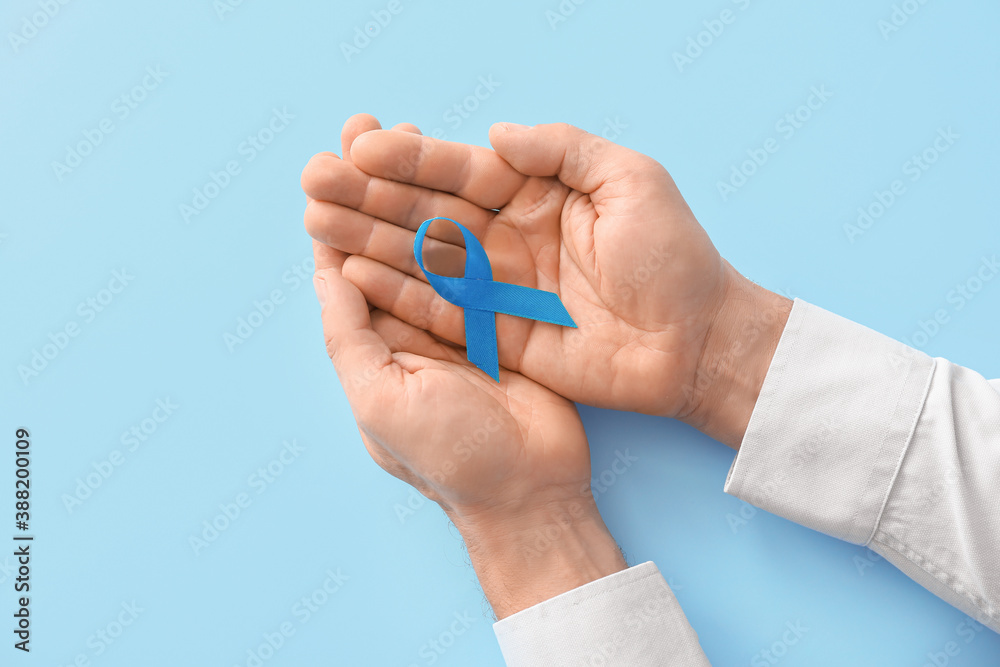 Fototapeta Male hands with blue ribbon on color background. Prostate cancer awareness concept