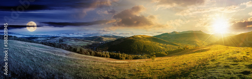 Fototapeta day and night time change concept above mountainous countryside landscape. panorama of a grassy rural field on the hill with sun and moon. village in the distant valley. clouds on the sky obraz