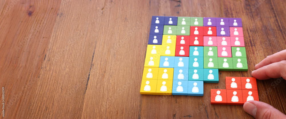 Fototapeta image of tangram puzzle blocks with people icons over wooden table ,human resources and management concept