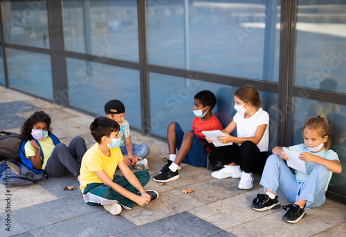 Fotografie, Obraz Group of preteen children in face masks resting outdoors in schoolyard during break in lessons