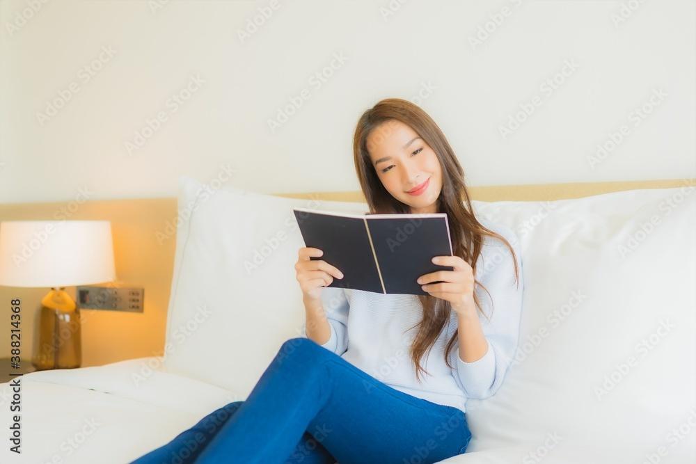 Fototapeta Portrait beautiful young asian woman read book on bed