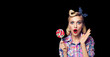 Leinwandbild Motiv Photo of beautiful very surprised woman with lollipop, in pinup style, over black color background