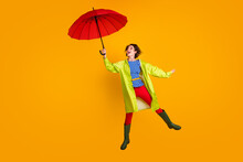 Full Length Photo Portrait Of Happy Woman Jumping Up Floating With Open Umbrella Looking At It Isolated On Bright Yellow Colored Background
