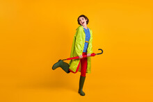 Full Length Photo Portrait Of Cute Girl With Umbrella On One Leg Laughing Isolated On Vivid Yellow Colored Background