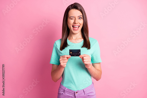 Obraz Photo portrait of woman holding credit card in two hands winking isolated on pastel pink colored background - fototapety do salonu