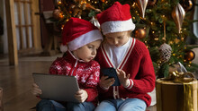 Wide Banner Panoramic View Of Little Brother And Sister Kids Have Fun Play On Gadgets On Winter Holidays At Home. Small Boy And Girl Children Look At Screen Enjoy Online Game Use Devices Together.